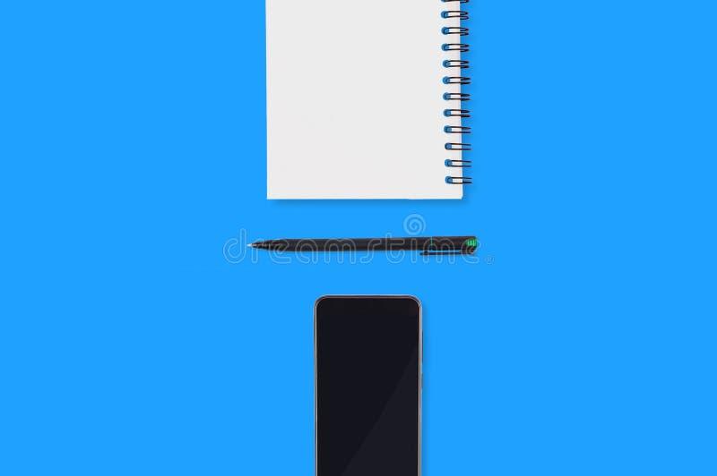Büroartikelpapiernotizblock mit Leerbelegplastikstift und schwarzem Smartphone verbreitete heraus auf blauer Tabelle Beschneidung stockfotos