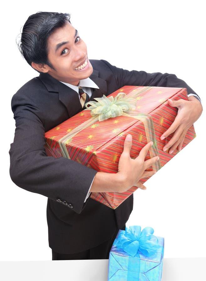 Bürobotengang, der Geschenk umklammert stockfoto