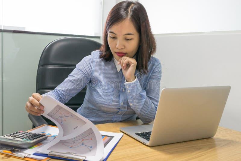 Bürodame, die Finanzdiagramme auf den Dokumentenberichten liest stockfotografie
