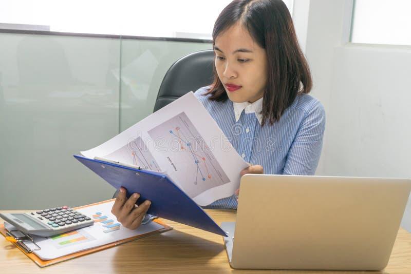 Bürodame, die Finanzverkaufsbericht im Büro liest stockbilder