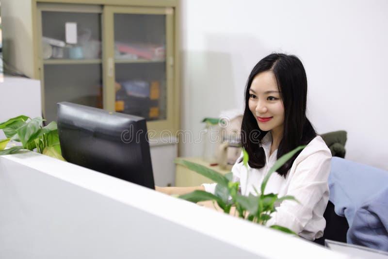 Bürodamen-Frauenmädchen Asiens chinesisches auf Getränkteearbeits-Laptop-Computer Lächelnabnutzungsgeschäftsbesetzungs-Anzugsarbe stockfoto