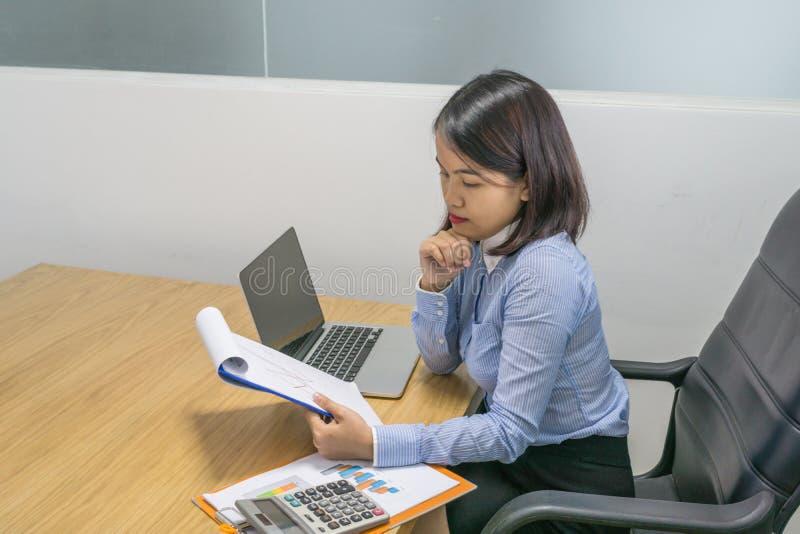 Bürodamenlesefinanzberichte im Büro stockfotos
