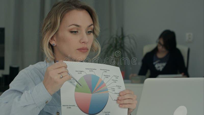 Bürofrau, die Kreisdiagramm Kollegen über Laptop erklärt stockbild