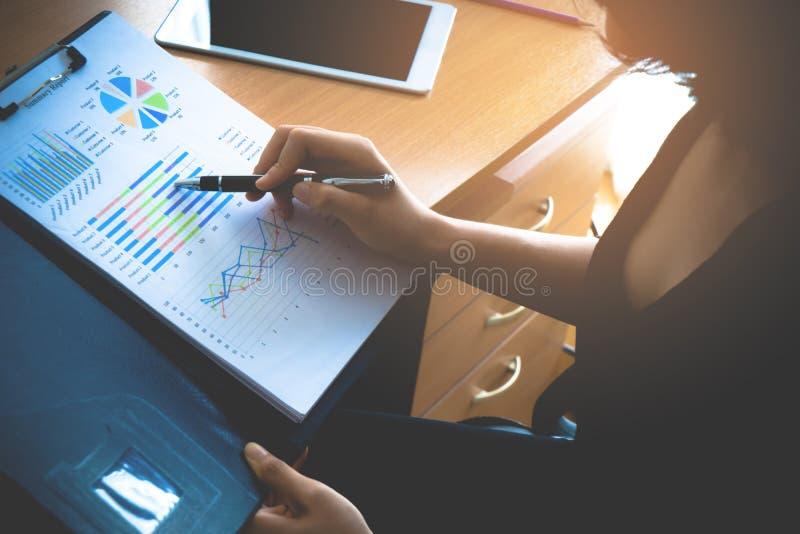 Bürofrau, die Verkäufe Leistungsblatt für das Geschäft Unternehmens analysiert stockbilder