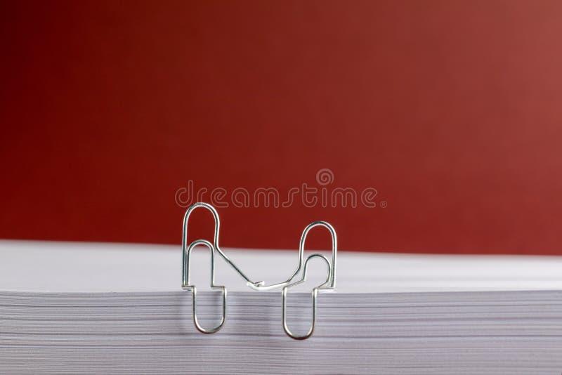Büroklammer-Händchenhalten auf Papierstapel auf rotem Hintergrund lizenzfreie stockbilder