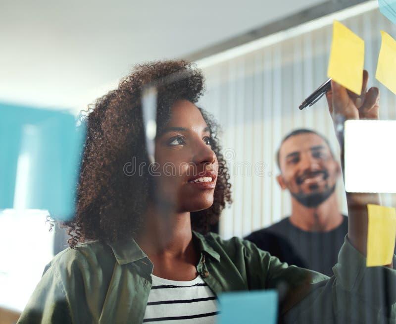 Bürokollegen, die Geschäftsideen und -pläne auf klebriges nicht schreiben lizenzfreies stockbild