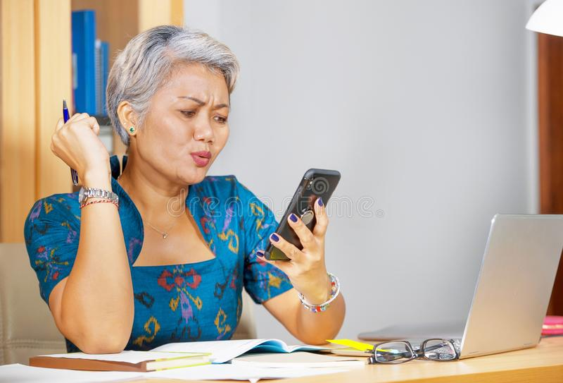 B?rolebensstilportr?t der attraktiven besorgten und betonten mittleren gealterten Asiatin, die Handy am Laptopcomputertisch verwe lizenzfreies stockbild