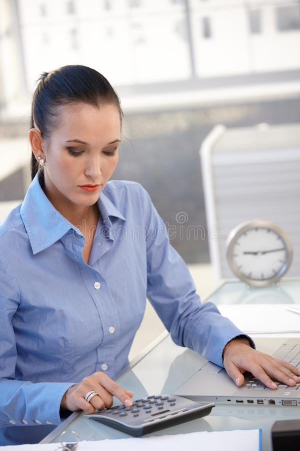 Büromädchen, das Taschenrechner verwendet stockfoto