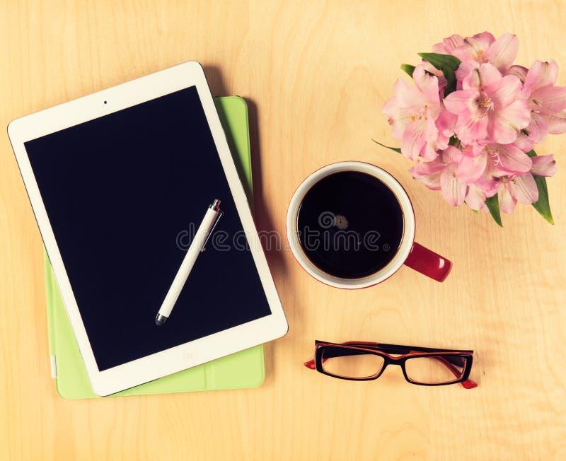 Bürotisch mit digitaler Tablette, Lesebrille und Tasse Kaffee Ansicht von oben stockbild