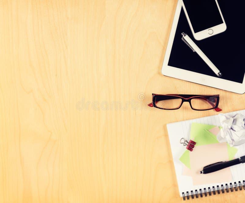 Bürotisch mit digitaler Tablette, Smartphone, Lesebrille und Notizblock Ansicht von oben lizenzfreie stockfotos