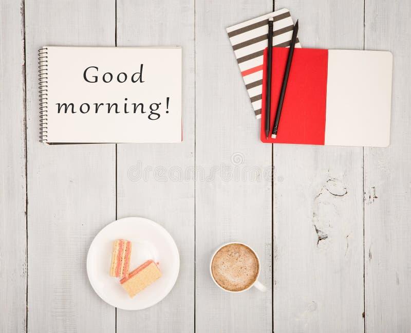 Bürotisch mit Notizblöcken und Text u. x22; Guten Morgen! u. x22; , Tasse Kaffee und Waffeln stockfoto