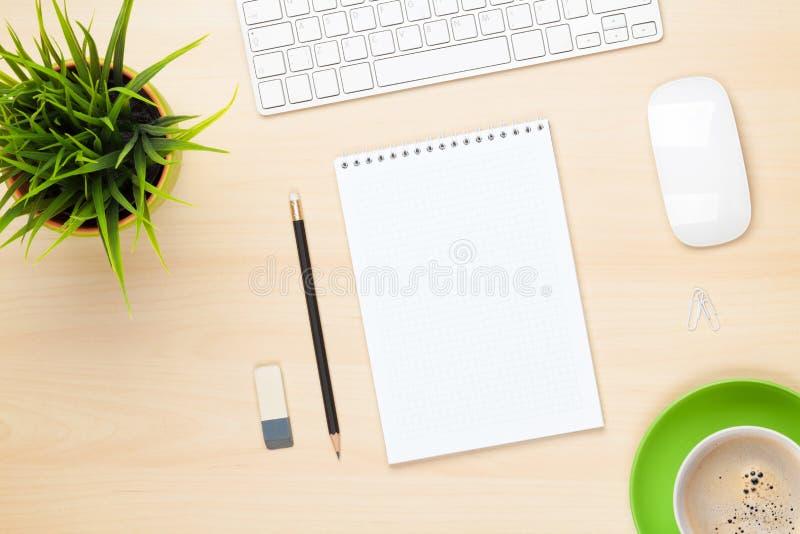 Bürotisch mit Notizblock, Computer, Kaffeetasse und Blume stockfotos