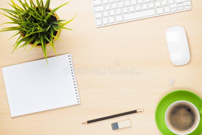 Bürotisch mit Notizblock, Computer, Kaffeetasse und Blume lizenzfreie stockbilder