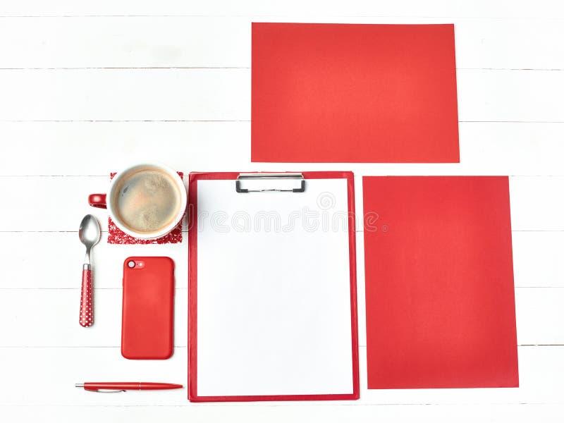 Bürotischschreibtisch mit Satz bunten Versorgungen, weißer leerer Notizblock, Schale, Stift auf weißem Hintergrund stockbilder
