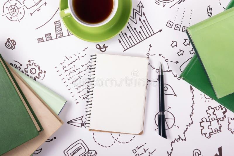Bürotischschreibtisch mit Versorgungen, leerer Notizblock, Schale, Stift auf weißem Hintergrund der Geschäftsstrategie Draufsicht lizenzfreie stockbilder