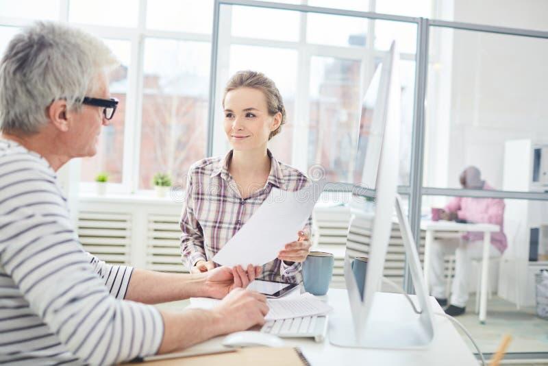 Bürovorsteher, die mit Papieren arbeiten stockfoto