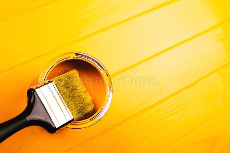 Bürste in der offenen Dose gelber Farbe auf frisch gemaltem hölzernem Brett stockfoto