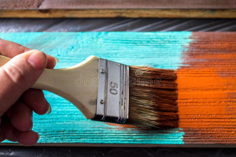 Bürste mit Farbe in der Hand Ein Mann malt blaue Bretter in einem braunen Pinsel stockfoto