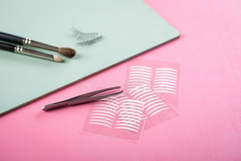 Bürsten, gefälschte Peitschen, Pinzette und doppelte Bänder der künstlichen Augenlidfalte für Augenmake-up auf rosafarbenem Paste stockbilder