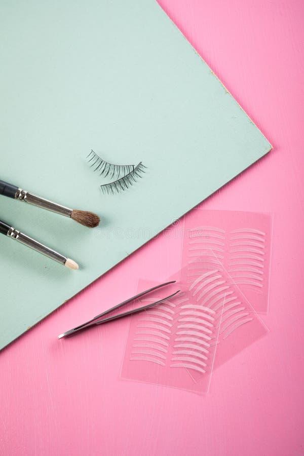 Bürsten, gefälschte Peitschen, Pinzette und doppelte Bänder der künstlichen Augenlidfalte für Augenmake-up auf rosafarbenem Paste stockbild