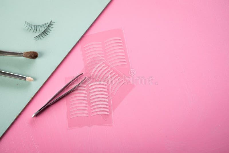 Bürsten, gefälschte Peitschen, Pinzette und doppelte Bänder der künstlichen Augenlidfalte für Augenmake-up auf rosafarbenem Paste lizenzfreie stockfotos