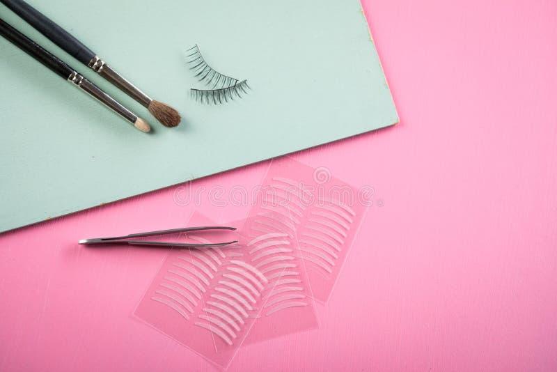 Bürsten, gefälschte Peitschen, Pinzette und doppelte Bänder der künstlichen Augenlidfalte für Augenmake-up auf rosafarbenem rosa  stockbild