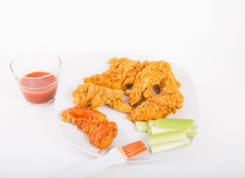 Bürstende scharfe Soße auf Hühnerstreifen stockfotografie