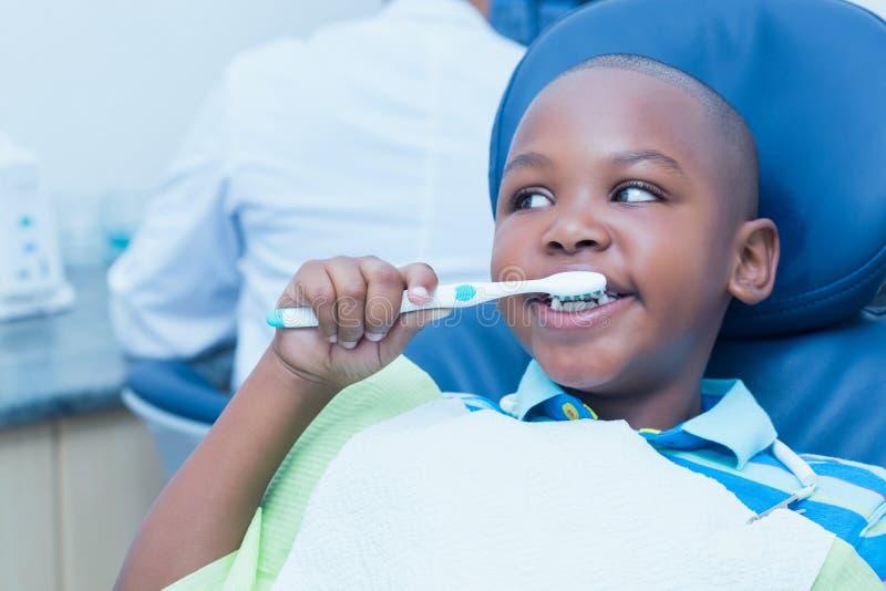 Bürstende Zähne des Jungen im Zahnarztstuhl stockbilder