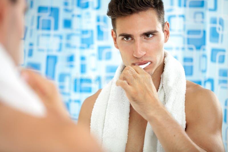 Bürstende Zähne des Mannes vor Spiegel lizenzfreies stockfoto