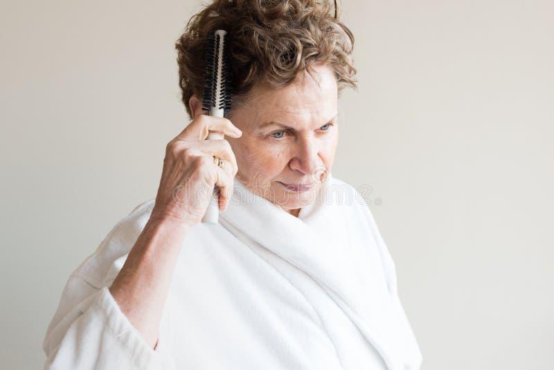 Bürstendes Haar der älteren Frau lizenzfreies stockbild