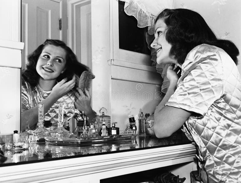 Bürstendes Haar der jungen Frau an der Frisierkommode (alle dargestellten Personen sind nicht längeres lebendes und kein Zustand  lizenzfreie stockfotos