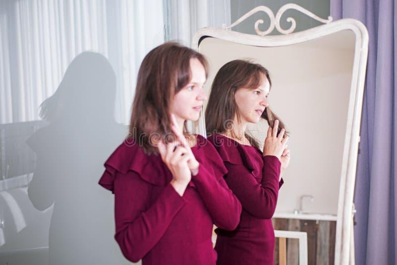 Bürstendes Haar der jungen Frau vor einem Spiegel lizenzfreie stockfotos