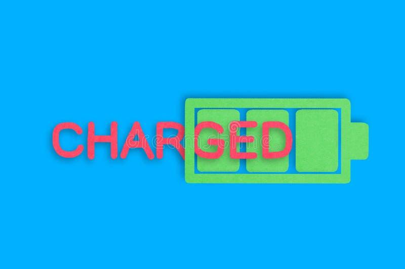 Büttenpapierikone der vollen Batterie mit grünen Zellen nahe dem roten Wort aufgeladen in der Mitte der blauen Tabelle Beschneidu lizenzfreie stockfotografie