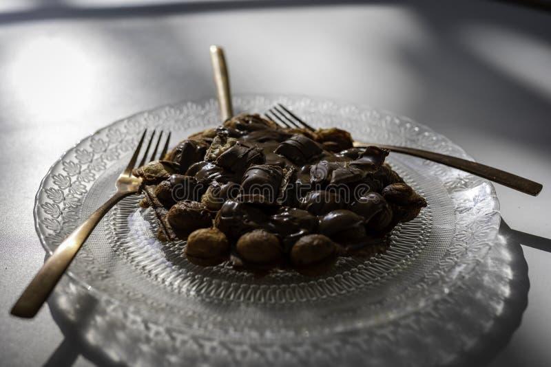 Bąbla gofr z czekoladą na przejrzystym talerzu z antykwarskim projektem z złotym rozwidleniem i nożem na białym drewnianym stole obraz stock
