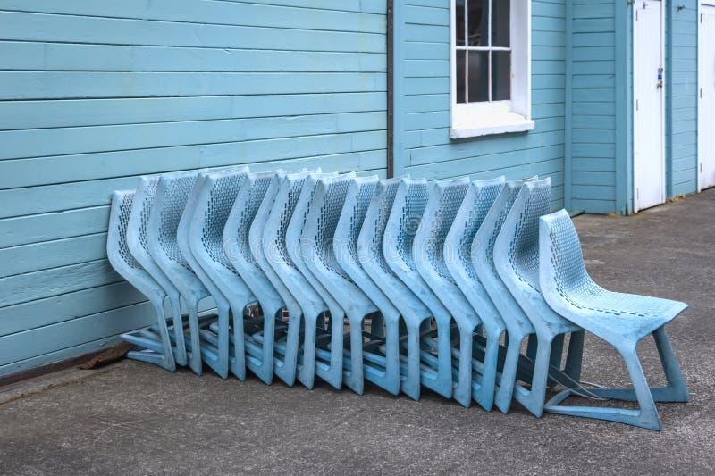 Błękitów krzesła przed drewnianym domem z rzędu obraz stock
