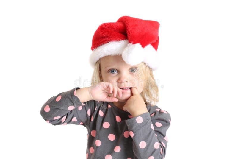 Błękit przyglądał się młodej dziewczyny z palcem w usta w Santa kapeluszu fotografia stock