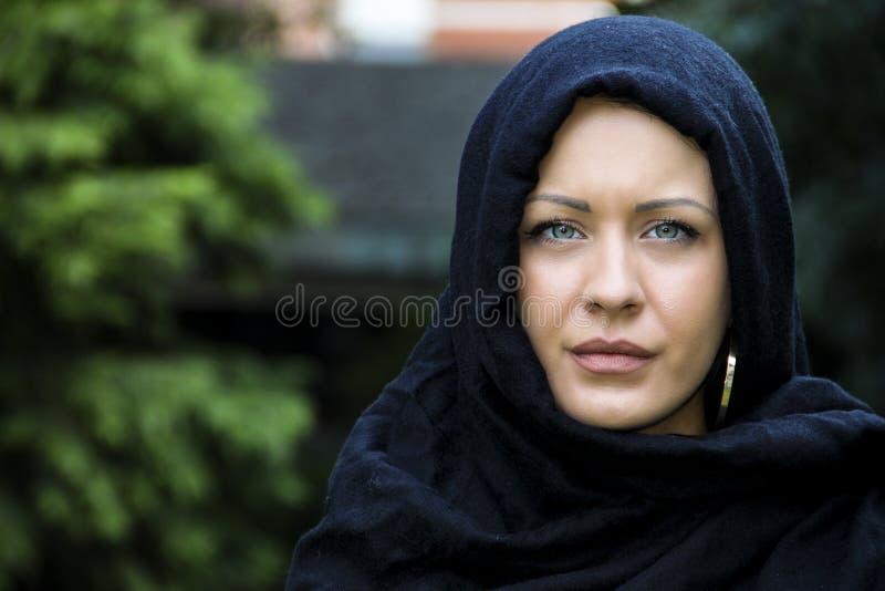 Błękit przyglądająca się muzułmańska dama w szaliku fotografia stock