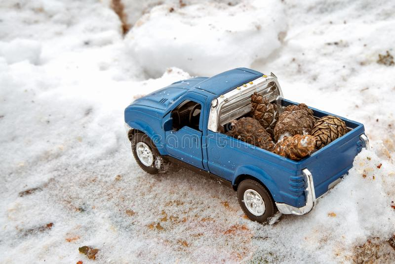 Błękit zabawkarska furgonetka w tartaku Wtykający przy snowdrift i trociny Niesie jedlinowych rożki z tyłu samochodowego ciała obrazy royalty free