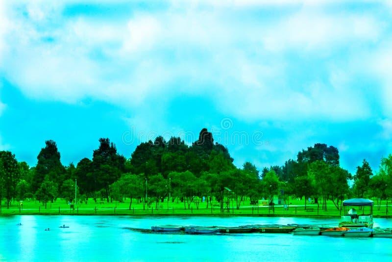 Błękita krajobraz z jeziorem i czółnami fotografia stock