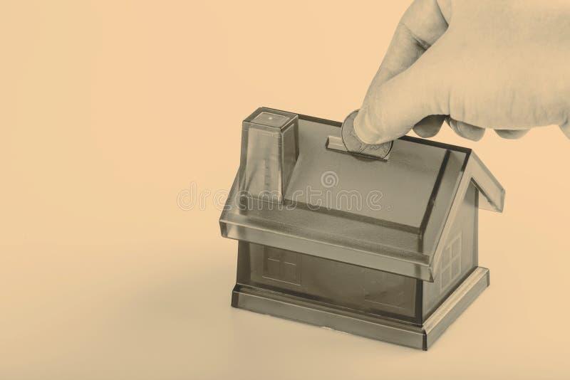 Błękita pieniądze Domowy pudełko z mężczyzna ręką i moneta na Białym tle obrazy royalty free