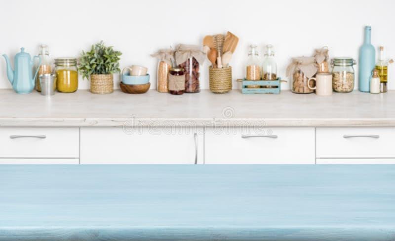 Błękita pusty drewniany kuchenny stół nad zamazanym karmowych składników tłem fotografia stock