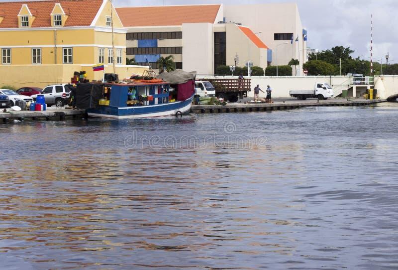 Błękitna łódź cumował za ikonowymi kolorowymi budynkami Curacao obraz royalty free