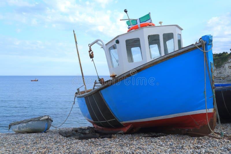 Błękitna łódź rybacka na otoczak plaży zdjęcie stock