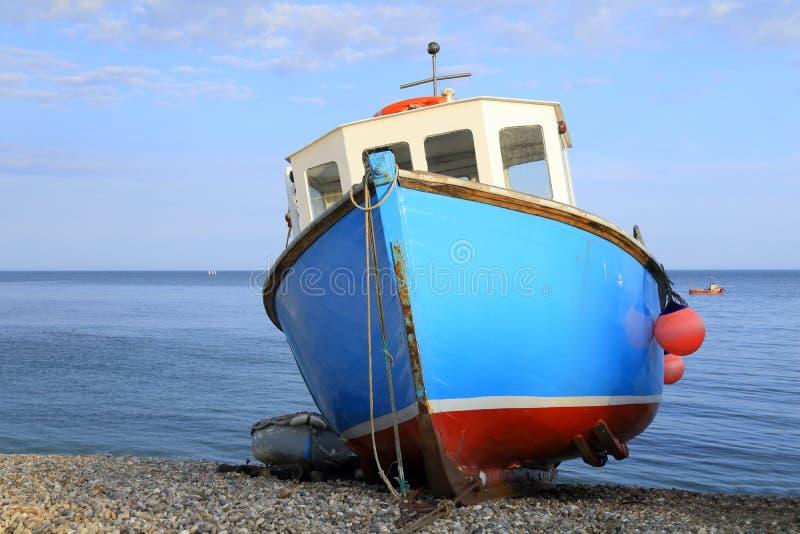 Błękitna łódź rybacka na otoczak plaży zdjęcia royalty free