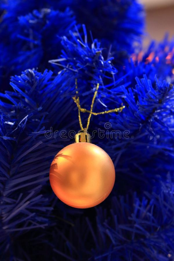Błękitna choinka z żółtą żarówką Błękitna sztuczna sosny gałąź z złotą piłką Świąteczna szczęśliwa nowy rok dekoracja obraz stock