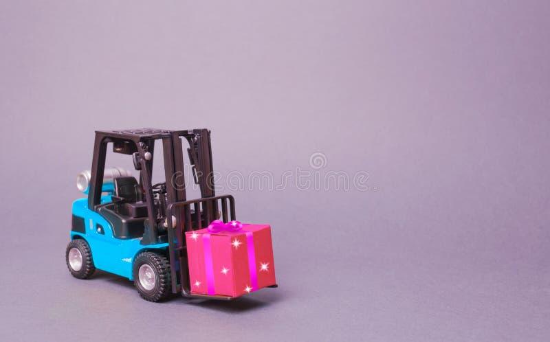 Błękitna forklift ciężarówka niesie różowego prezenta pudełko z łękiem Zakup i dostawa teraźniejszość handel detaliczny, pomija i obrazy royalty free