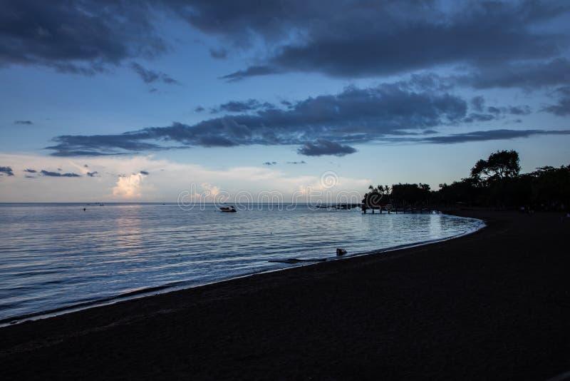 Błękitna godzina nad spokojnym oceanem i czarny piasek wyrzucać na brzeg fotografia stock