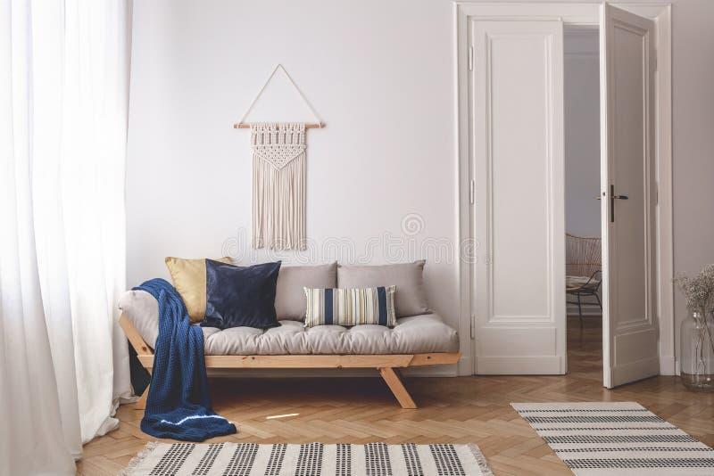 Błękitna koc i poduszki na drewnianej leżance w białym żywym izbowym wnętrzu z dywanikami i drzwi Istna fotografia obrazy stock
