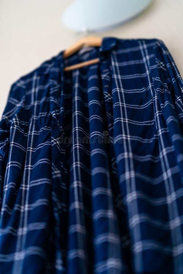 Błękitna koszula z lampasami Wiesza na ścianie w Żywym pokoju fotografia stock