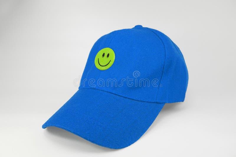 Błękitna nakrętka z smiley szczęśliwą twarzą odizolowywającą na białym tle obrazy royalty free